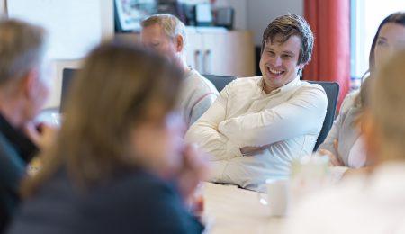 Ansatte i Lierhus sitter rundt et bord. En ler. Foto.